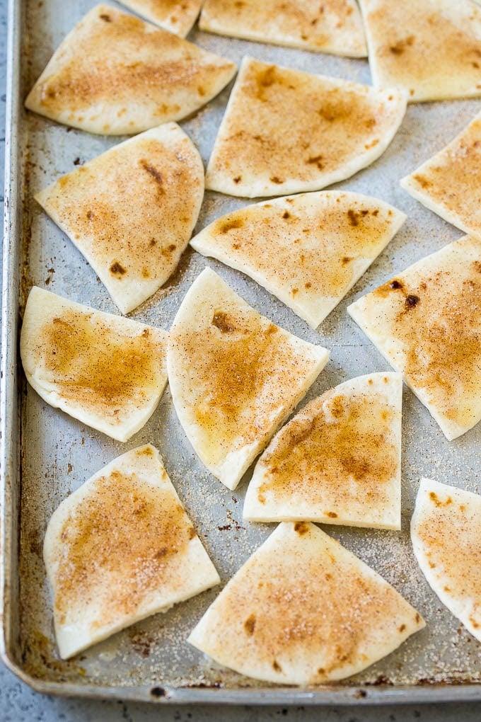 Tortilla wedges coated in cinnamon sugar on a baking sheet.