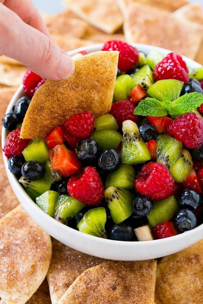 Fruit salsa with a cinnamon sugar chip scooping some out.