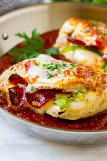 Chicken breasts stuffed with pepperoni and cheese in a pan of marinara sauce.