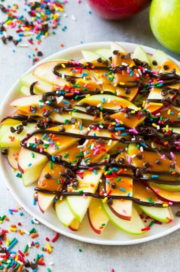A plate of sliced apples topped with caramel and chocolate sauces, rainbow sprinkles and mini chocolate chips