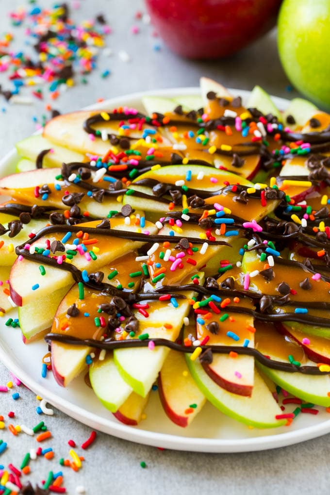 A plate of red and green sliced apples drizzled with caramel and chocolate, then topped with rainbow sprinkles and chocolate chips.