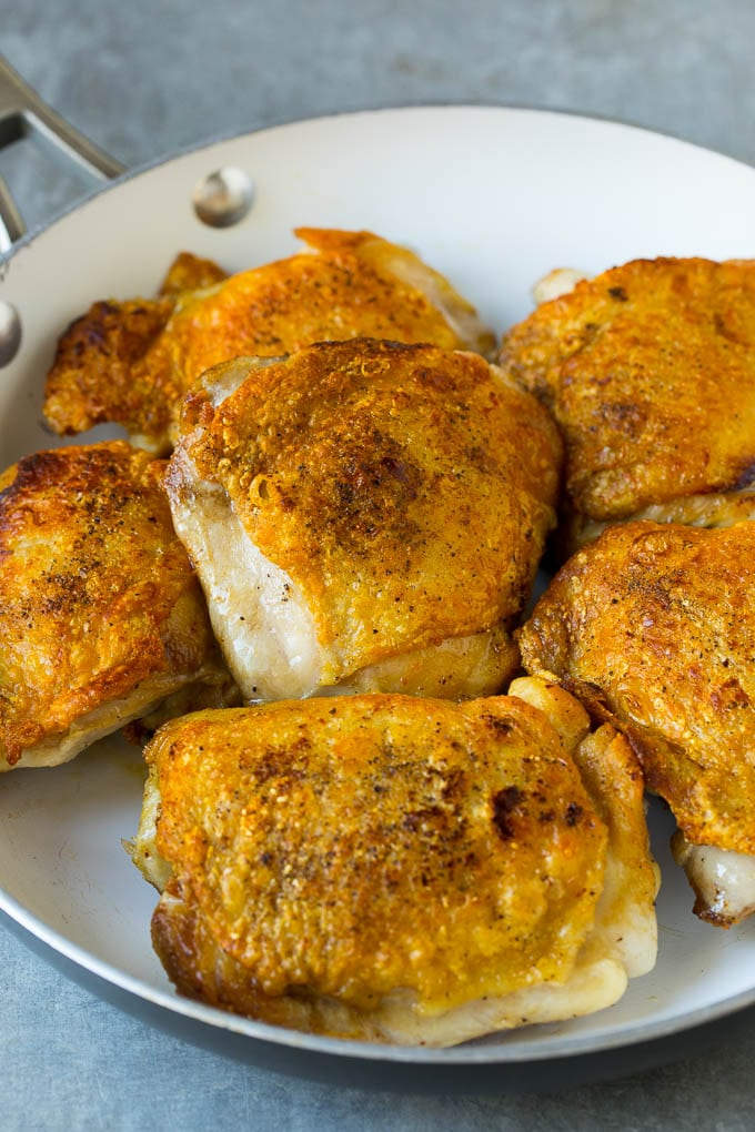 Seared chicken thighs in a pan.