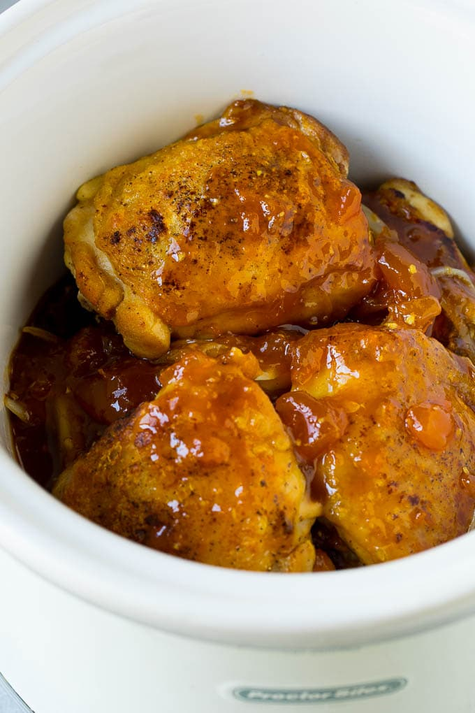 Chicken thighs in a slow cooker topped with a mixture of apricot jam, soy sauce and ginger.