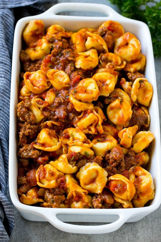 A dish of cheese tortellini tossed in meat sauce.
