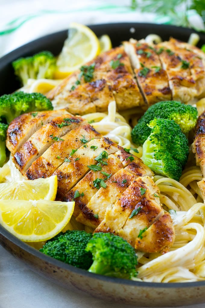 Sliced chicken breast with broccoli on top of creamy linguine pasta.