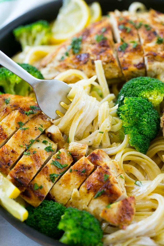 A forkful of creamy lemon pasta surrounded by chicken and broccoli.