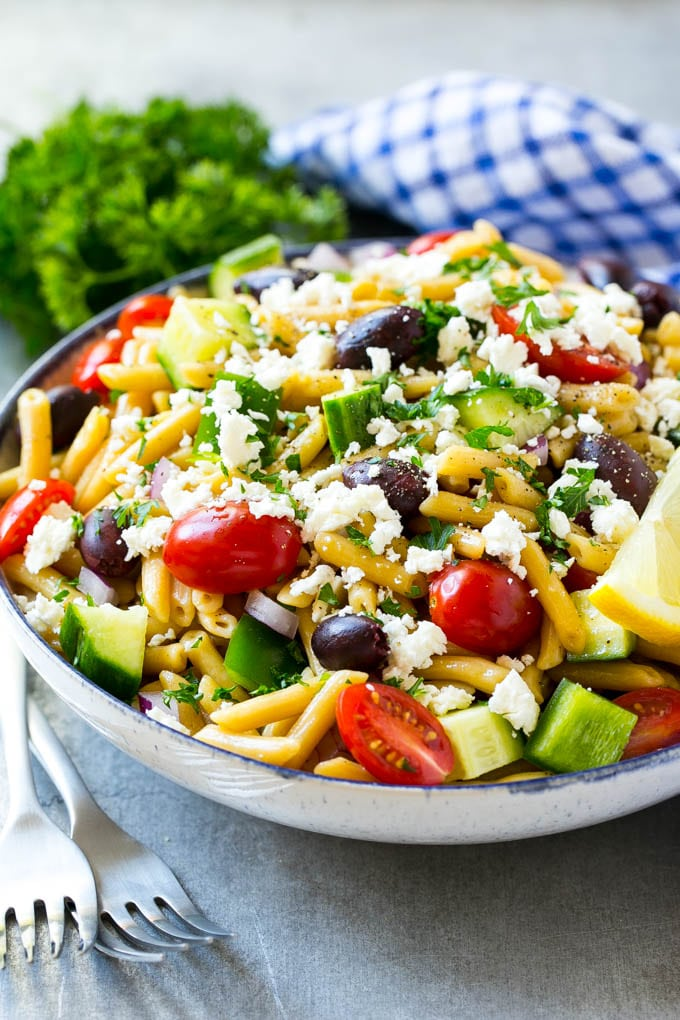 A bowl of penne pasta tossed with colorful vegetables and topped with feta cheese.