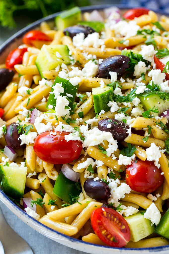 A close up of Greek pasta with penne pasta, cherry tomatoes, cucumber and olives.