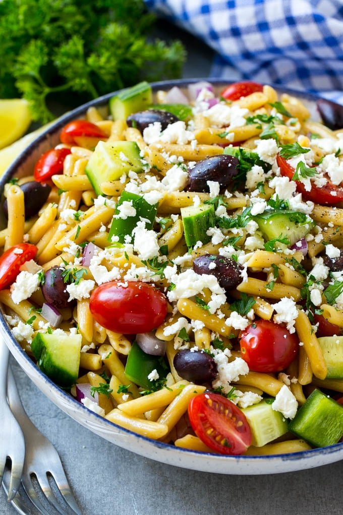 A bowl of Greek pasta with tomatoes, cucumbers, feta cheese and olives.