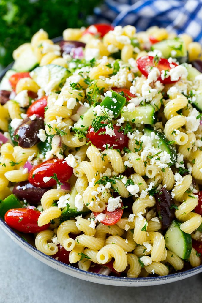A bowl of Greek pasta salad loaded with feta cheese, olives, tomatoes, cucumber and bell peppers.