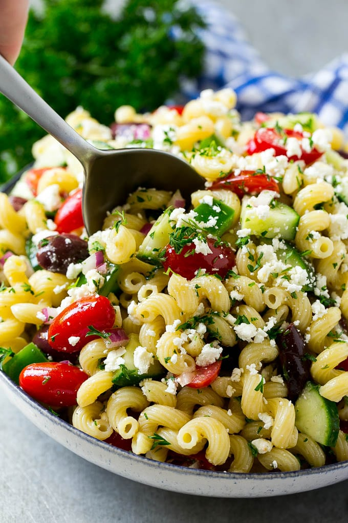 A bowl of Greek pasta salad with a serving spoon in it.
