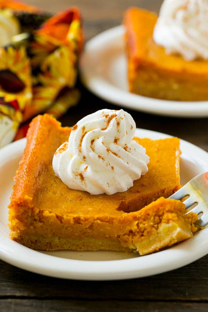 A piece of pumpkin gooey butter cake with a fork in it.