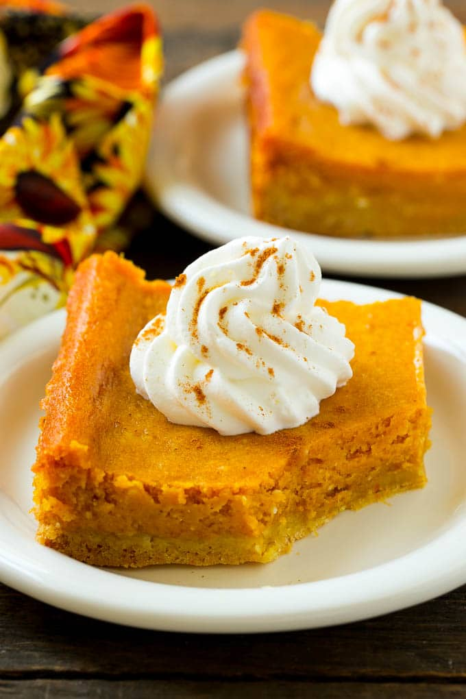 A slice of pumpkin gooey butter cake with a bite taken out of it.