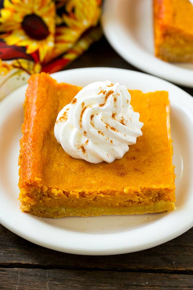 A slice of pumpkin gooey butter cake topped with whipped cream.