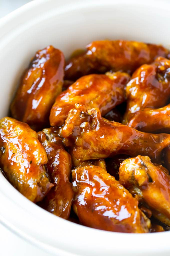 A slow cooker full of barbecue chicken wings.