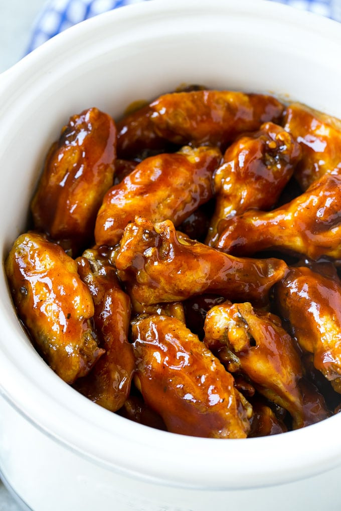 A slow cooker full of chicken wings that have been cooked in barbecue sauce.