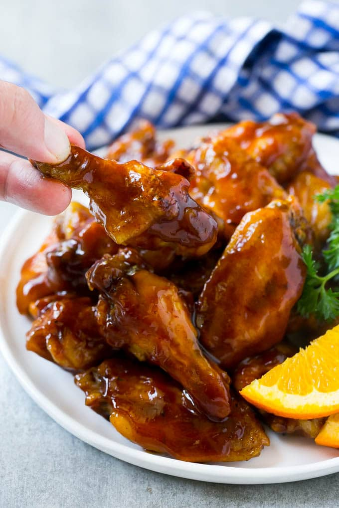 A plate of slow cooker barbecue chicken wings with a hand reaching out to take one.