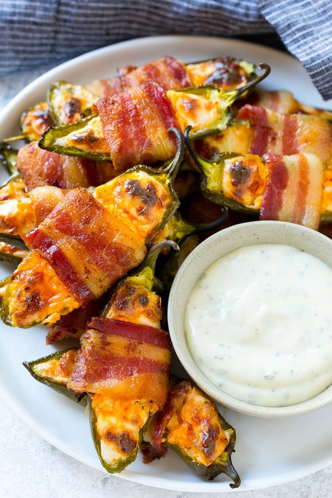 A plate full of bacon wrapped jalapeno poppers with a side of ranch for dipping.