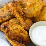 Crispy baked chicken fingers on a plate with ranch dip.