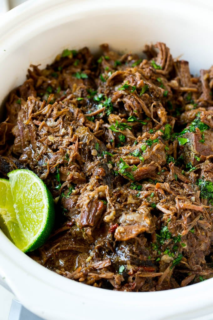 A slow cooker full of barbacoa beef.