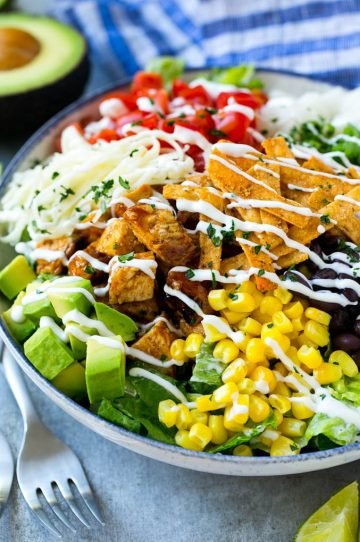 A bowl of BBQ chicken salad topped with a drizzle of ranch dressing.