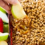 A hand scooping out a serving of caramel apple dip.