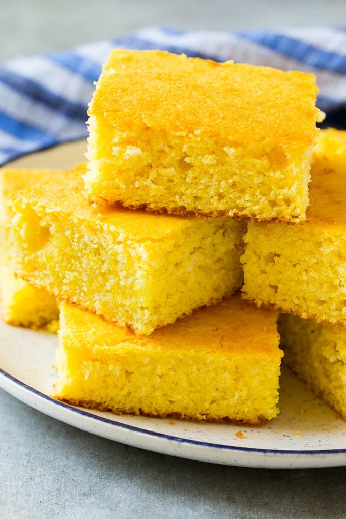 A plate full of squares of honey cornbread.