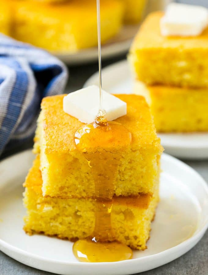 A stack of cornbread topped with butter and honey