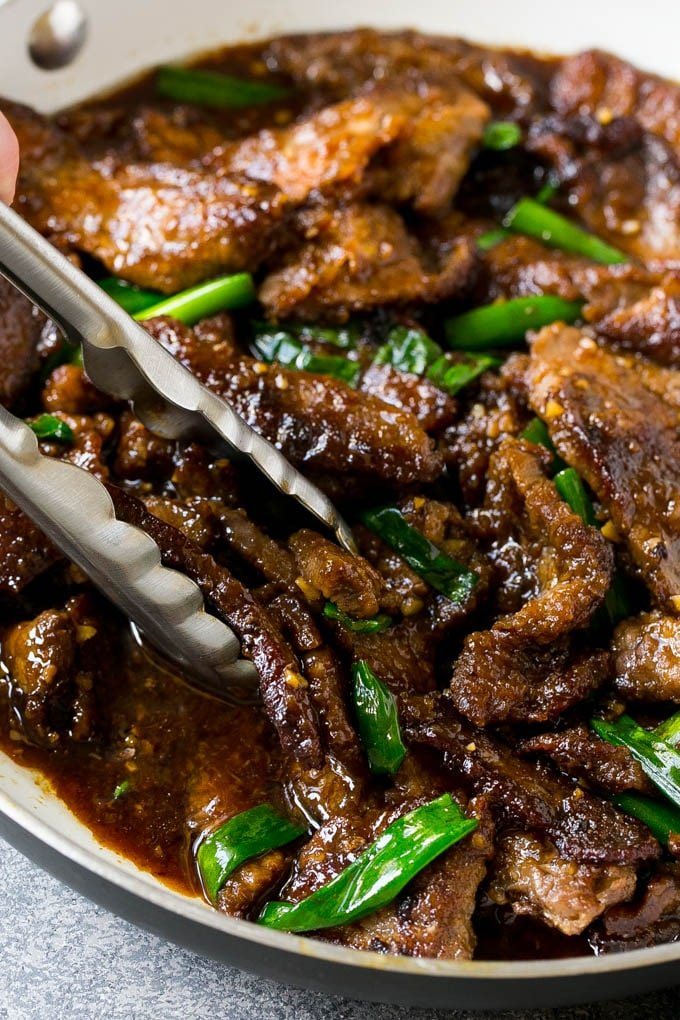 A pan of Mongolian beef with tongs in it.