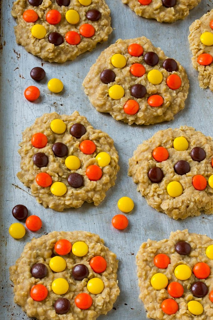 A sheet pan full of no bake peanut butter cookies with candies on top.