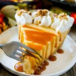 A fork cutting into a slice of no bake pumpkin cheesecake.