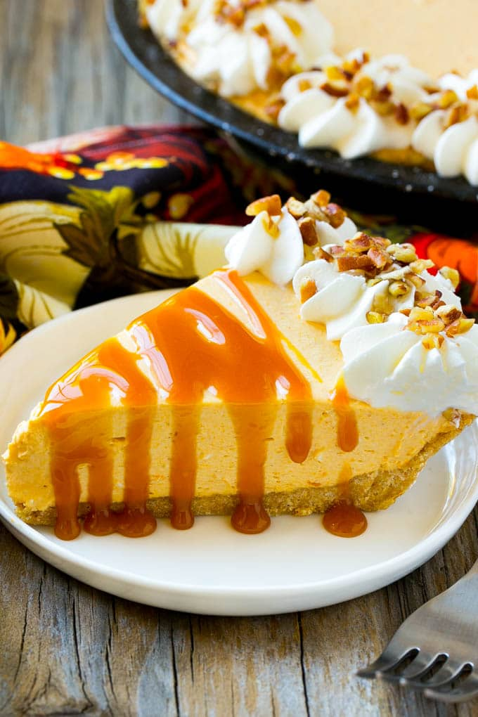 A piece of no bake pumpkin flavored cheesecake topped with caramel.