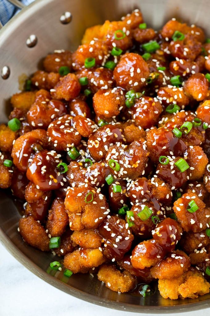 A pan of popcorn shrimp in an Asian sesame sauce.