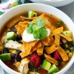 A bowl full of slow cooker chicken tortilla soup with avocado, sour cream and tortilla strips.