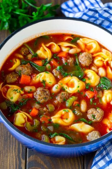 A pot of tortellini soup with tomato broth, Italian sausage, spinach and carrots.