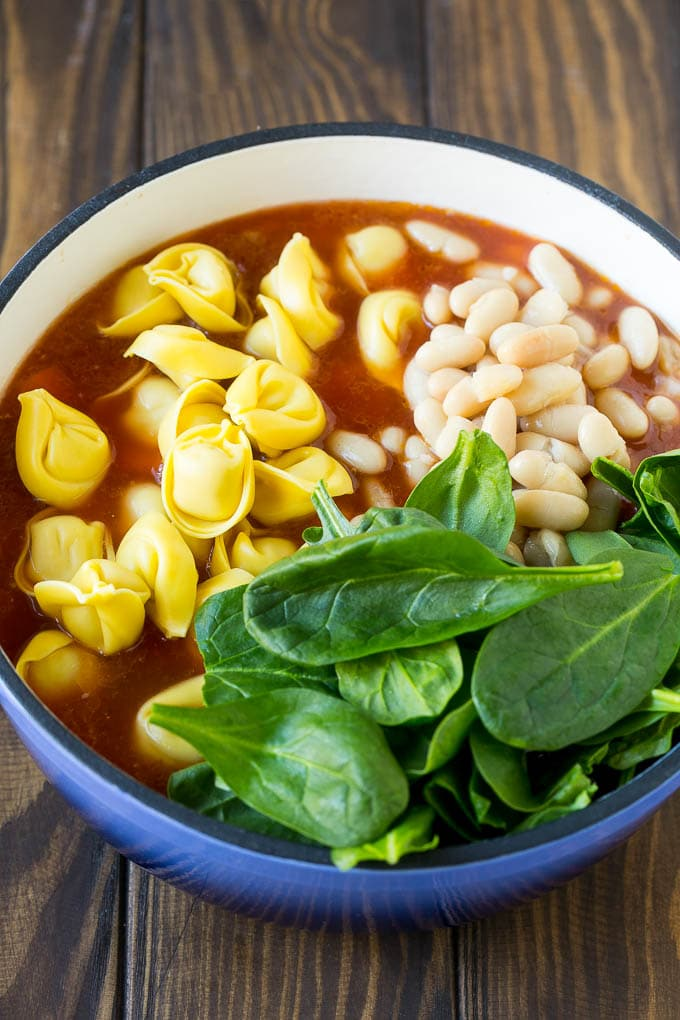 A pot of soup with tortellini, spinach leaves and white beans.