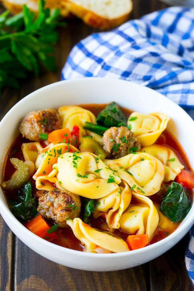 A bowl of tortellini soup with sausage and vegetables.