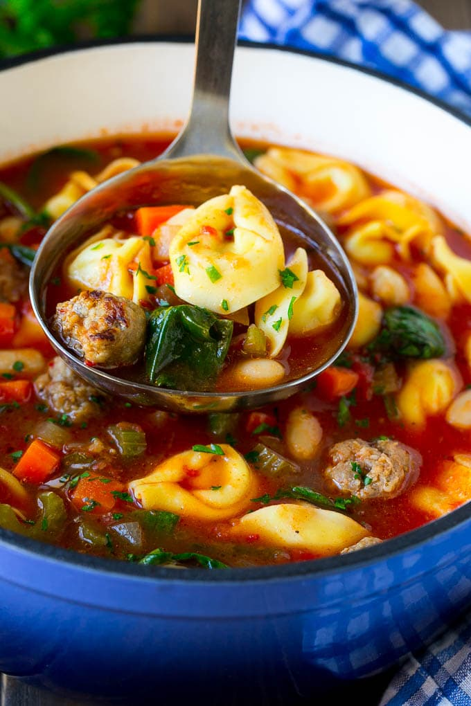 A ladle serving up a portion of tortellini soup.