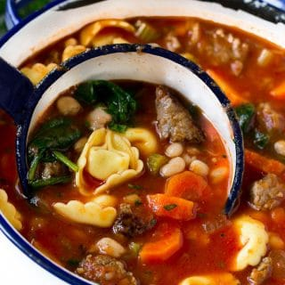 A ladle full of tortellini soup with sausage, spinach, beans and veggies.