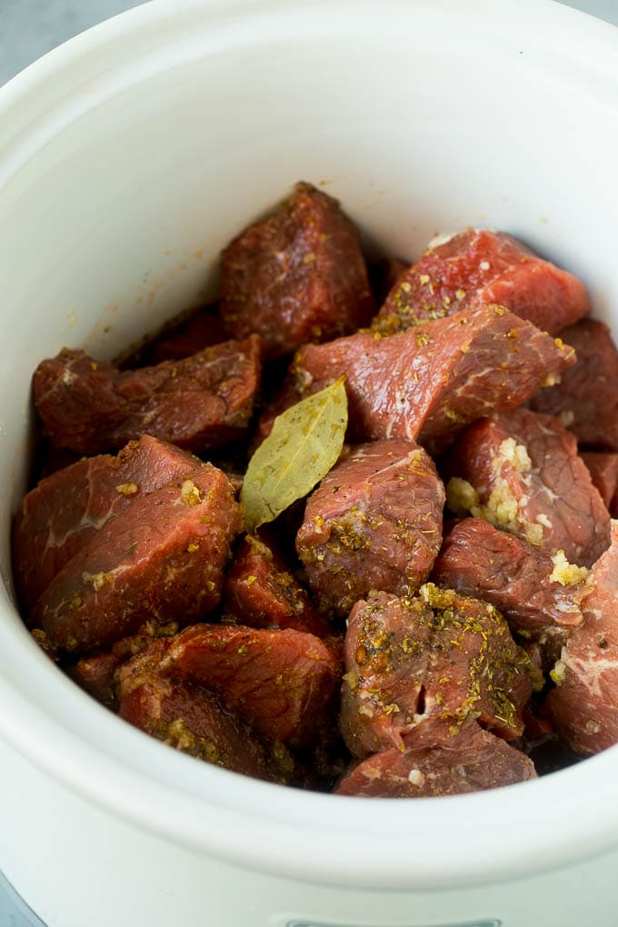 Chunks of beef tossed with beef broth, spices and a bay leaf in a crock pot.