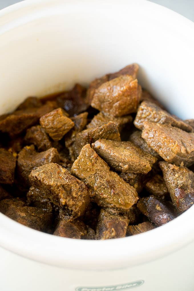 Cooked barbacoa cubes in a slow cooker.