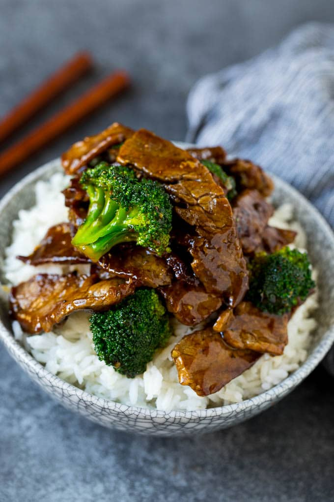 A bowl of beef and broccoli stir fry served over rice.
