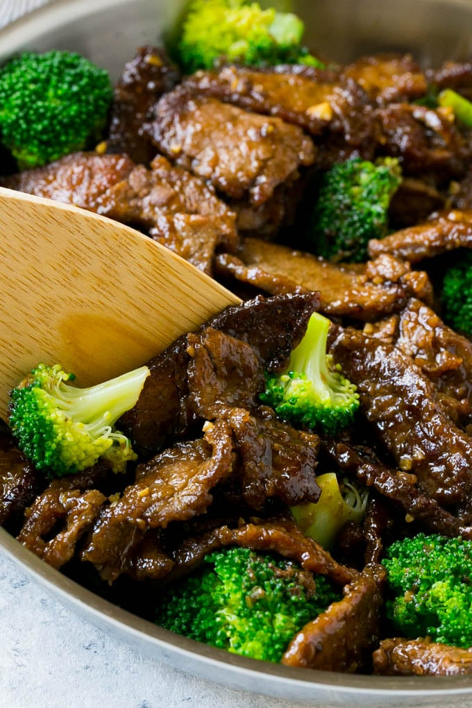 A pan of beef and broccoli stir fry with a spatula in it.