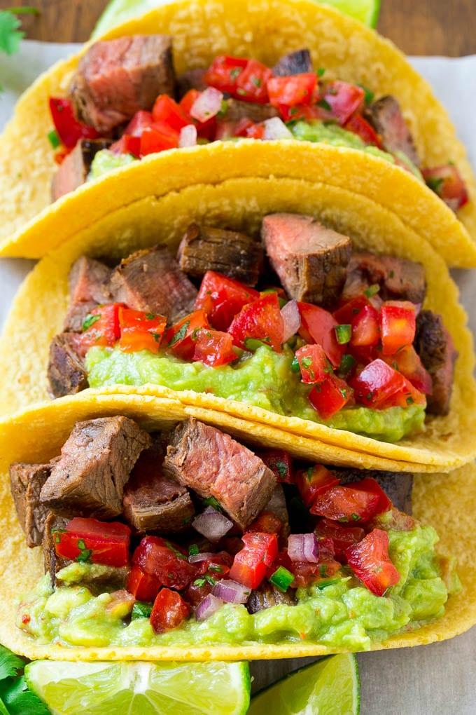 A platter of carne asada tacos topped with guacamole and pico de gallo.
