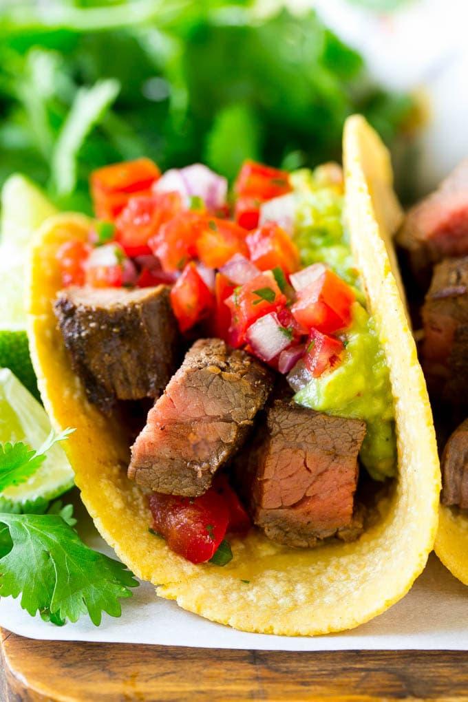A carne asada taco with beef, guacamole and pico de gallo.