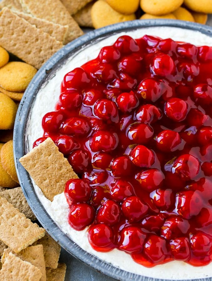 A plate of cherry cheesecake dip with a graham cracker in it.