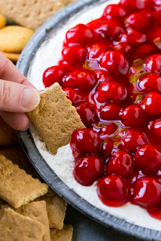 A graham cracker scooping up a serving of cherry cheesecake dip.