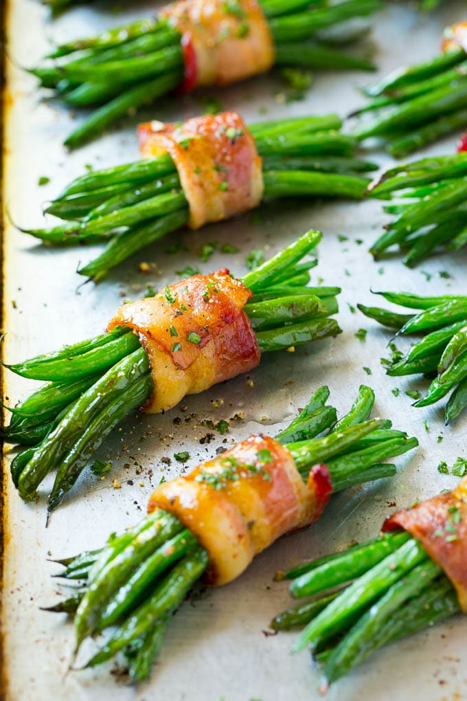 Bacon wrapped green bean bundles on a sheet pan.