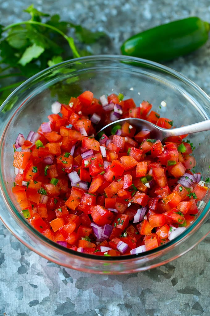 Tomatoes, cilantro, onion and jalapeno mixed together in a glass bowl.