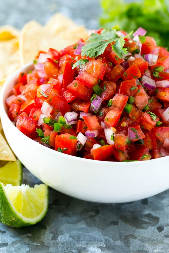 A bowl of homemade pico de gallo surrounded by tortilla chips.
